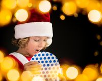 Surprised child holding Christmas gift box Royalty Free Stock Photo