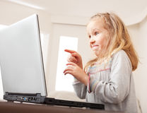 Surprised child with laptop indoors Royalty Free Stock Photos