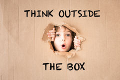Surprised child looking through hole of cardboard. `Think outside the box` text Stock Images