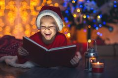Surprised child opening magic Christmas book. Xmas holiday concept Stock Photography