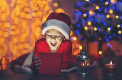 Surprised child opening magic Christmas present. Royalty Free Stock Photo