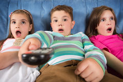 Surprised children watching TV. At home Royalty Free Stock Photos