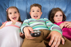 Surprised children watching TV. At home Stock Photos