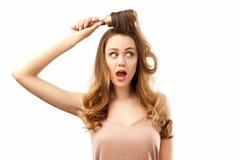Surprised choc? a la mujer joven con el pelo hermoso largo, los peina y abrir su boca en el asombro El concepto de cuidado del ca foto de archivo