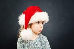 Surprised Christmas Child in Santa Hat on Blackboard Stock Photos