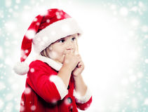 Surprised Christmas Child in Santa Hat on Snowy Background Stock Photos