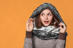 Surprised christmas girl wearing knitted wear scarf. Excited  beautiful smiling girl, winter concept, isolated over orange backgro Stock Photo