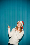 Surprised christmas girl wearing a santa hat Stock Image
