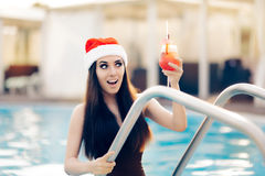 Surprised Christmas Woman with Cocktail at the Pool. Funny girl celebrating Christmas in a spa resort Royalty Free Stock Photo