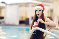 Surprised Christmas Woman with Cocktail at the Pool. Funny girl celebrating Christmas in a spa resort Royalty Free Stock Photos
