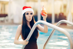 Surprised Christmas Woman with Cocktail at the Pool. Funny girl celebrating Christmas in a spa resort Royalty Free Stock Image