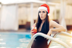 Surprised Christmas Woman with Cocktail at the Pool. Funny girl celebrating Christmas in a spa resort Stock Photo