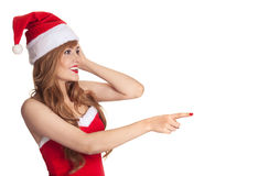 Surprised christmas woman wearing a santa hat. Shows on copyspace isolated over a white background Royalty Free Stock Photo