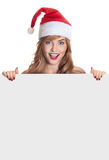 Surprised christmas woman wearing a santa hat. Holding empty blank isolated over a white background Stock Image