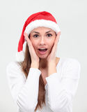 Surprised christmas woman wearing a santa hat. Smiling isolated over a white background Stock Photo