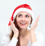 Surprised christmas woman wearing a santa hat. Smiling isolated over a white background Royalty Free Stock Photo