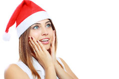 Surprised christmas woman. Wearing a santa hat smiling isolated over a white background Stock Image