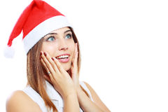 Surprised christmas woman. Wearing a santa hat smiling isolated over a white background Royalty Free Stock Photography