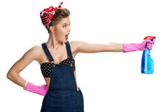 Surprised cleaning girl wearing pink rubber protective gloves holding spray Royalty Free Stock Photo