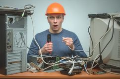 Computer repairman. Computer technician engineer. Support service. Surprised Computer network technician is crimping a network cable by crimper tool in his royalty free stock images