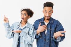 Surprised a confondu les couples africains dans des chemises de denim regardant l'appareil-photo Images libres de droits