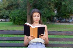 Surprised confused and with widely open eyes woman is reading a book on the bench in the park.  stock images