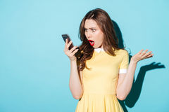 Surprised confused woman in dress looking at mobile phone. Portrait of a surprised confused woman in dress looking at mobile phone isolated over blue background Royalty Free Stock Photo