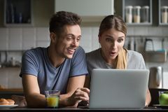 Surprised couple amazed with online shopping sale looking at lap. Surprised young couple feeling amazed with online shopping sale looking at laptop excited with stock photography