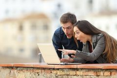 Surprised couple checking laptop content in a balcony. With a town in the background stock photography