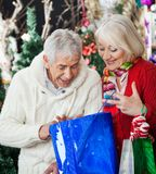 Surprised Couple Looking Into Shopping Bag Stock Images