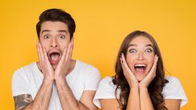 Surprised couple screaming and touching face over background. Surprised couple screaming and touching face over yellow background royalty free stock photo