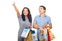 Surprised couple at shopping pointing up. Surprised young couple with shopping bags looking up and pointing to copy space isolated on white background Stock Photography