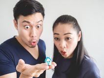 Surprised couple with small house in hand. Surprised Asian couple lover. Man show the small house in hand Stock Image