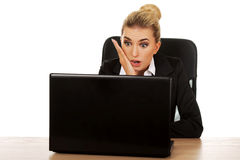 Surprised and curious businesswoman cannot believe what she sees in the laptop screen Stock Image