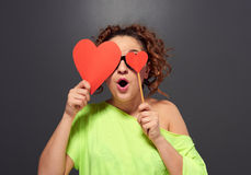 Surprised curly woman cover eyes with two red hearts Stock Photography