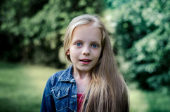 Surprised cute little blond girl at summer field. Stock Images