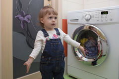 Surprised cute little girl with clothes doing laundry in home interior. Cute little girl doing laundry in home interior. Mother`s helper. 2 year old stock images