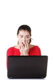 Surprised and disgusted woman working on laptop. Royalty Free Stock Image