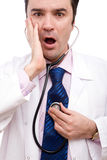 Surprised doctor. Surprised medical doctor with his stethoscope on white Stock Photo