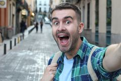 Surprised ecstatic man taking a selfie stock photography