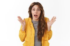 Surprised emotive wondered girl curly chestnut hairstyle drop jaw confused impressed raise hands up full disbelief. Amazement standing white background stock images