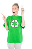 Surprised environmental activist wearing recycling tshirt holding light bulb Royalty Free Stock Images