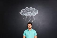 Surprised erstaunte den Mann, der unter dem raincloud steht, das auf Tafelhintergrund gezeichnet wurde Lizenzfreie Stockfotografie