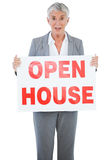 Surprised estate agent holding sign for open house Stock Photo