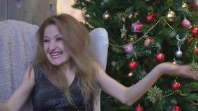 Surprised excitó a la mujer de griterío feliz en fondo del árbol de navidad almacen de video