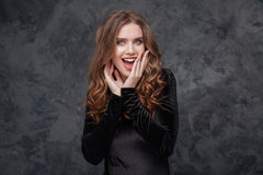 Surprised excited beautiful young woman in black dress. Over grey background Stock Photos
