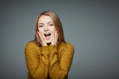 Surprised excited blond girl in sweater screaming of joy royalty free stock photos