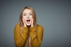 Surprised excited blond girl in sweater screaming of joy stock photo
