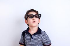 Surprised or excited boy looking through sunglasses, studio shoo. T on white. Fantasy, children, fashion and lifestyle concept royalty free stock images