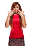 Surprised excited brunette woman throws up his. Hands opened her mouth isolated in red dress Royalty Free Stock Images